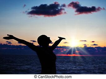 vrouw, silhouette, op, ondergaande zon