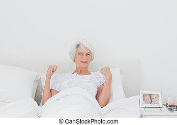 vrouw stretching, en, optillende armen, in bed