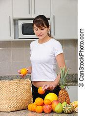 vrouw, uitpakken, kruidenierswaren, in de keuken