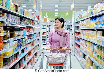 vrouw, voortvarend, boodschappenwagentje, kijken naar, goederen, in, supermarkt
