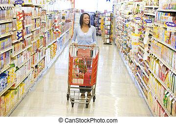 vrouw, voortvarend, wagentje, langs, supermarkt, gangpad