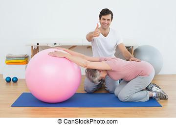 vrouw, yoga, op, bal, therapist, duimen, senior, gesturing