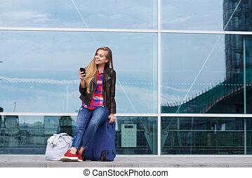 vrouw zitten, beweeglijk, reizen, nakomeling kijkend, telefoon, koffer