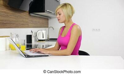 vrouw zitten, draagbare computer, jonge, het typen, thuis, tafel, keuken
