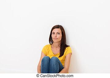 vrouw zitten, in, de, vloer, leunende tegen een muur