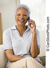 vrouw zitten, in, woonkamer, gebruik, telefoon, en, het glimlachen