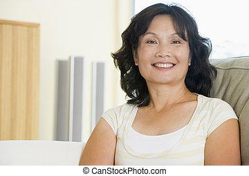 vrouw zitten, in, woonkamer, het glimlachen