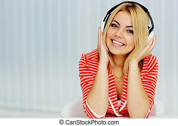 vrouw zitten, jonge, jas, muziek luisteren, tafel,...