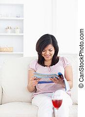vrouw zitten, sofa, terwijl, magazine, lezende