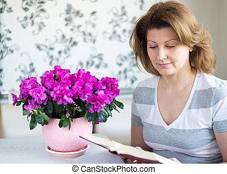 vrouw zitten, terwijl, boek, tafel, lezende