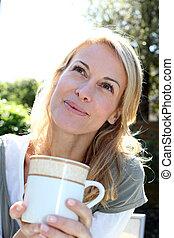 vrouw zitten, thee beker, buiten, blonde , verticaal