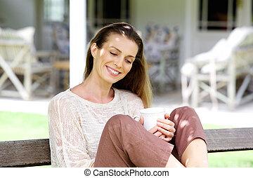 vrouw zitten, theekop, buiten, het glimlachen