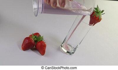 vrouwelijke hand, gieten, in, een, glas, vers fruit, melk, en, aardbei smoothie, drank