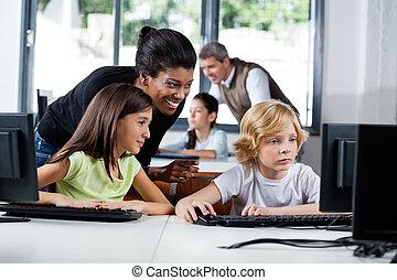 vrouwelijke leraar, helpen, schooljeugd, in, het gebruiken computer