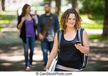 vrouwelijke student, gebruik, cellphone, op, campus