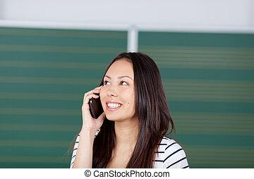vrouwelijke student, gebruik, smartphone, in, klaslokaal