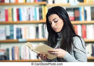 vrouwelijke student, het lezen van een boek, in, bibliotheek