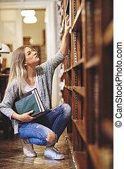 vrouwelijke student, het onderzoeken, in, bibliotheek