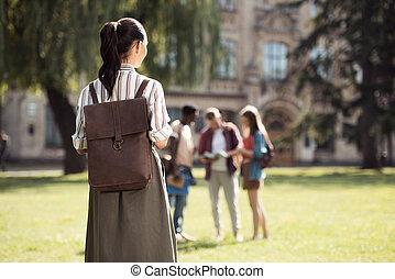 vrouwelijke student, kijken naar, klasgenoten