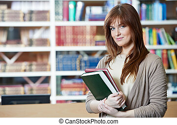 vrouwelijke student, meisje, met, boekjes , in, bibliotheek