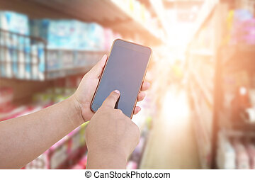 vrouwen, gebruiken, mobiele telefoon, en, benevelde beeld, van, supermarket., shoppen , concept.