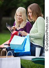 vrouwen, met, het winkelen zakken, gebruik, tablet pc, buitenshuis
