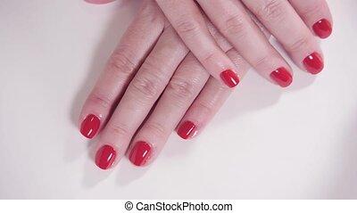 vrouwenhanden, met, manicure, en, rood, lak, op, een, witte , tafel, in, de, beauty, salon., closeup, van, hand, van, een, jonge, woman.