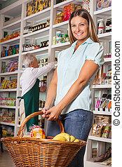 vrouwenholding, boodschappenmand, met, verkoper, in, achtergrond