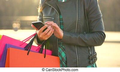 vrouwenholding, haar, het winkelen zakken, in, haar, hand, en, gebruik, een, smartphone
