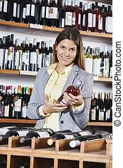 vrouwenholding, rode wijn, fles, in, winkel