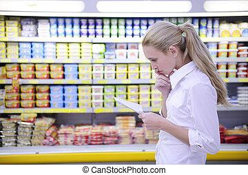 vrouwenlezing, haar, het winkelen lijst, in, de, supermarkt