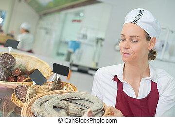 vrouwlijk, arbeider, met, assortiment, van, salami, op, winkel