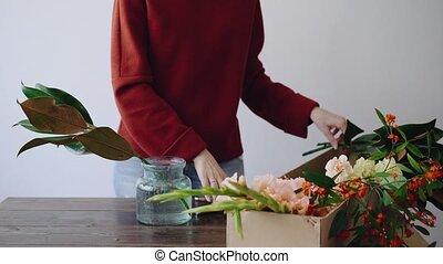 vrouwlijk, bloemist, zet, bloemen, in, een, glas vaas, en,...