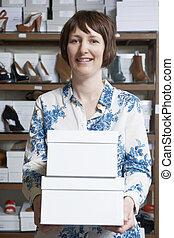 vrouwlijk, eigenaar, van, schoenenwinkel, dragende dozen