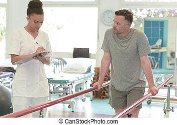 vrouwlijk, fysiotherapeut, staand, door, patiënt, wandelende