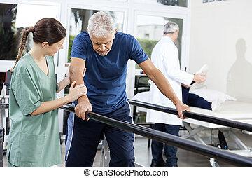 vrouwlijk, fysiotherapeut, staand, door, patiënt, wandelende, tussen, paral