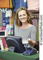 vrouwlijk, kassier, op, verkopen bureau, met, kredietkaart machine