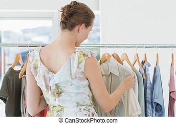 vrouwlijk, klant, het selecteren, kleren, op, kleding arak, in, winkel