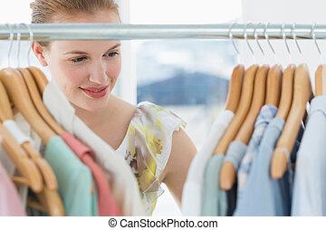 vrouwlijk, klant, het selecteren, kleren, op, winkel