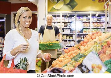 vrouwlijk, klant, vasthouden, appel, in, supermarkt