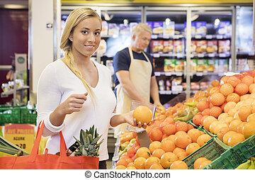 vrouwlijk, klant, vasthouden, sinaasappel, in, grocery slaan op