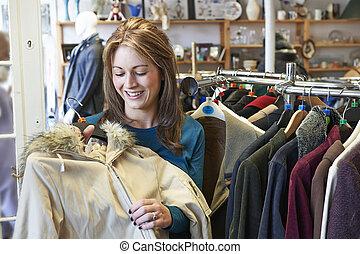 vrouwlijk, koper, in, thrift winkel, kijken naar, kleren
