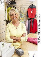 vrouwlijk, omzet assistent, in, de opslag van de kleding