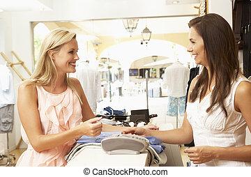 vrouwlijk, omzet assistent, op, kassa, van, de opslag van de kleding, met, klant