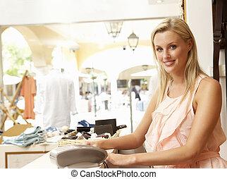 vrouwlijk, omzet assistent, op, kassa, van, de opslag van de kleding