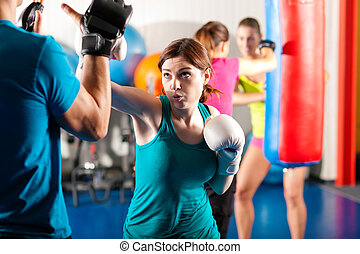 vrouwlijk, schopboxer, met, trainer, in, sparring