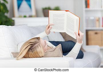 vrouwlijk, sofa, terwijl, boek, student lezen, het liggen