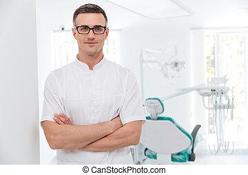 vrouwlijk, tandarts, staand, met, zijn, handen, gekruiste