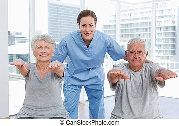vrouwlijk, therapist, helpen, senior koppel, met, oefeningen