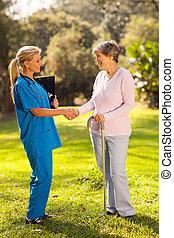 vrouwlijk, verpleegkundige, groet, het terugkrijgen, senior, patiënt
